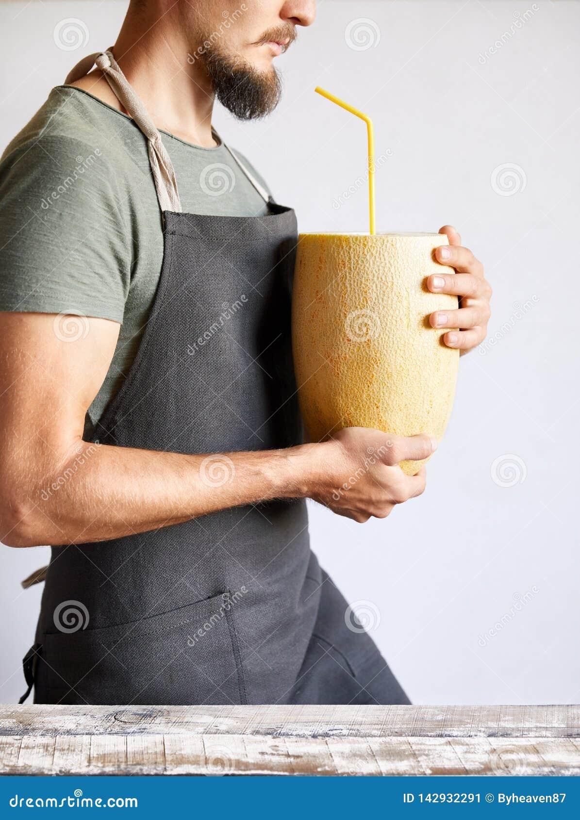 Человек держа желтую дыню с smoothie