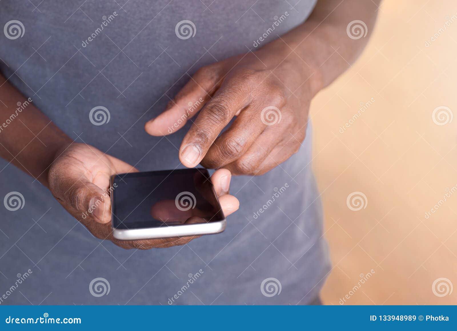 Человек держа и используя смартфон для работы или развлечений