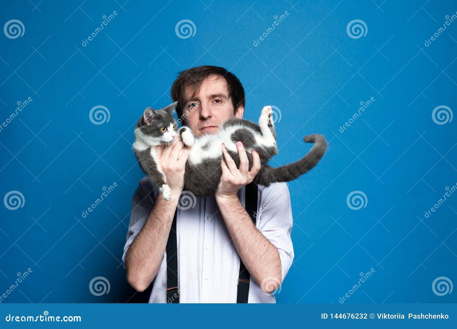 человек держа на заднем милом сером коте около стороны и усмехаться