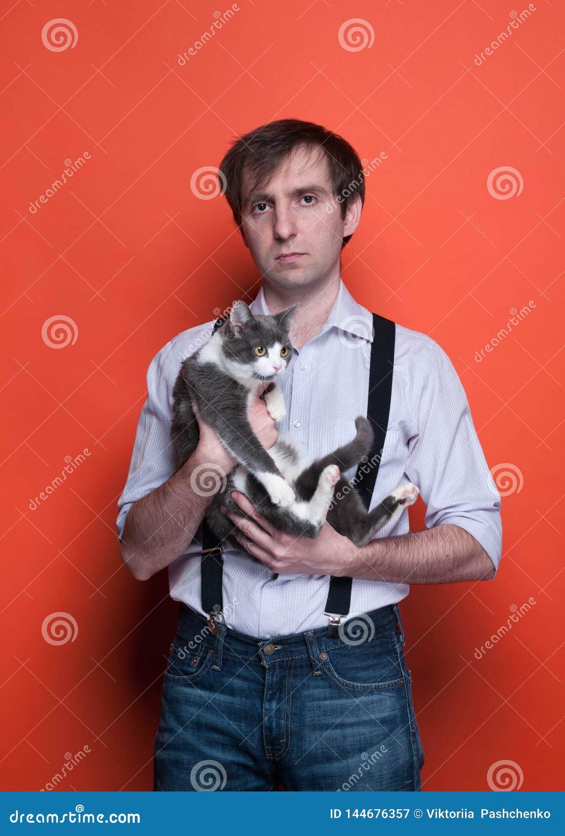 Человек держа прелестного серого кота с белыми лапками на оранжевой п