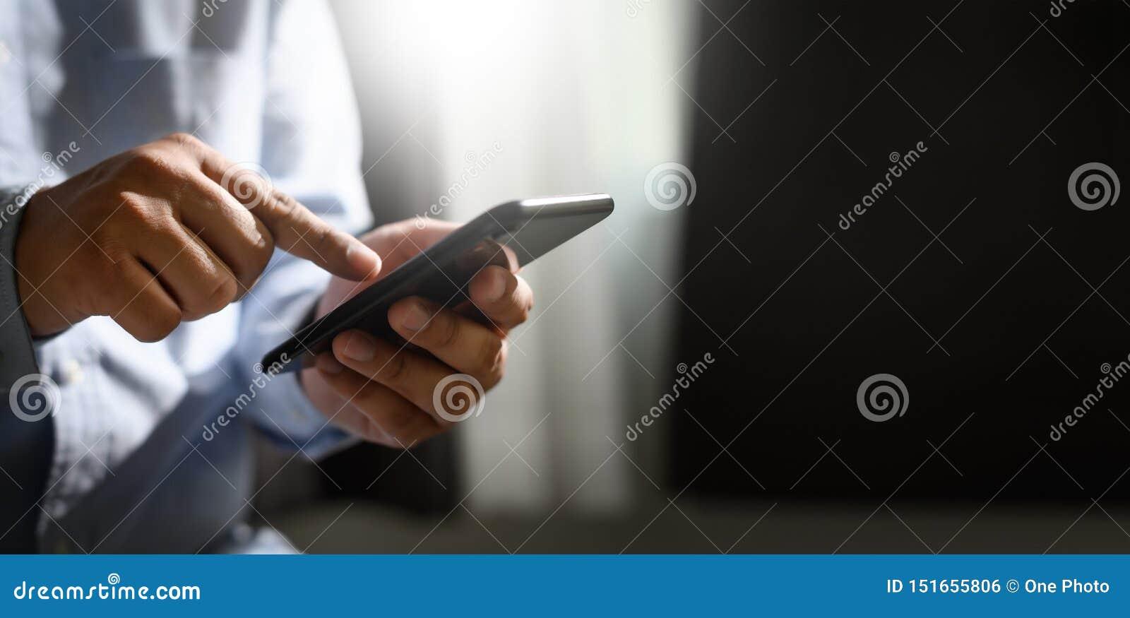 Человек держа руки en и используя цифровой телефон мобильного телефона планшета с пустым scree космоса экземпляра