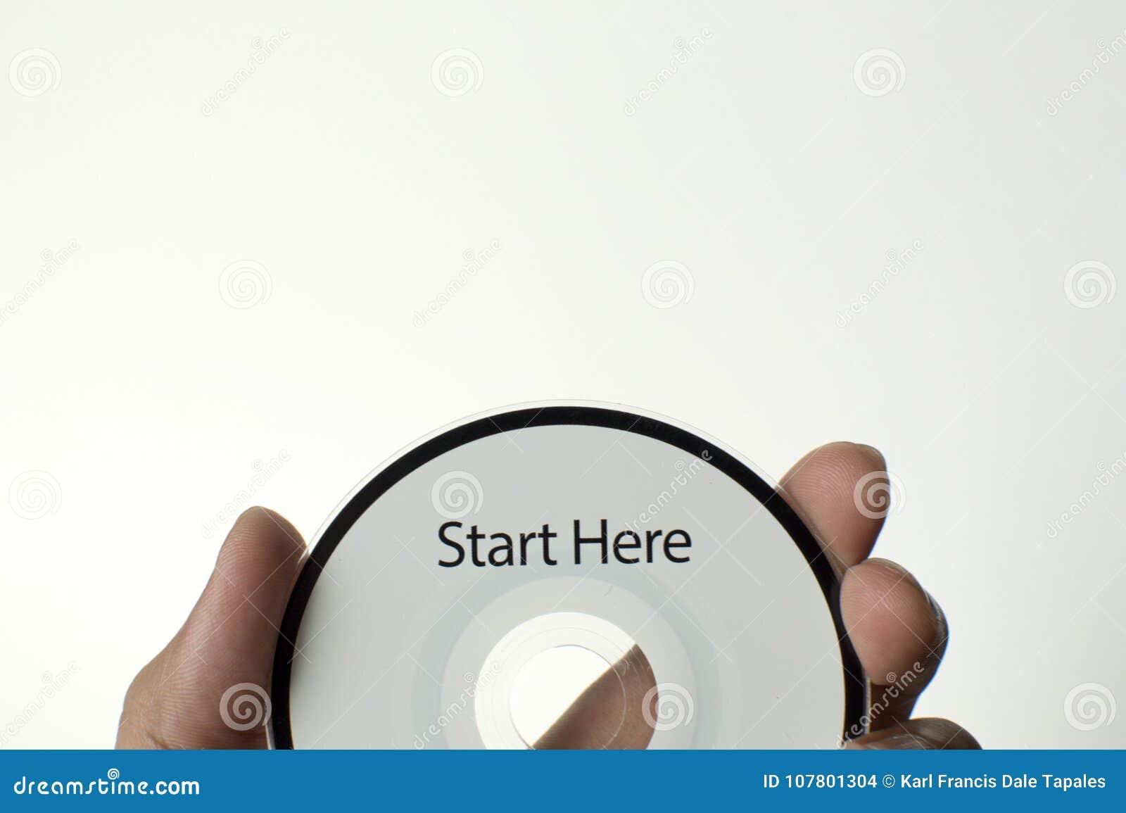 Человек держит компактный диск с сообщением старта здесь