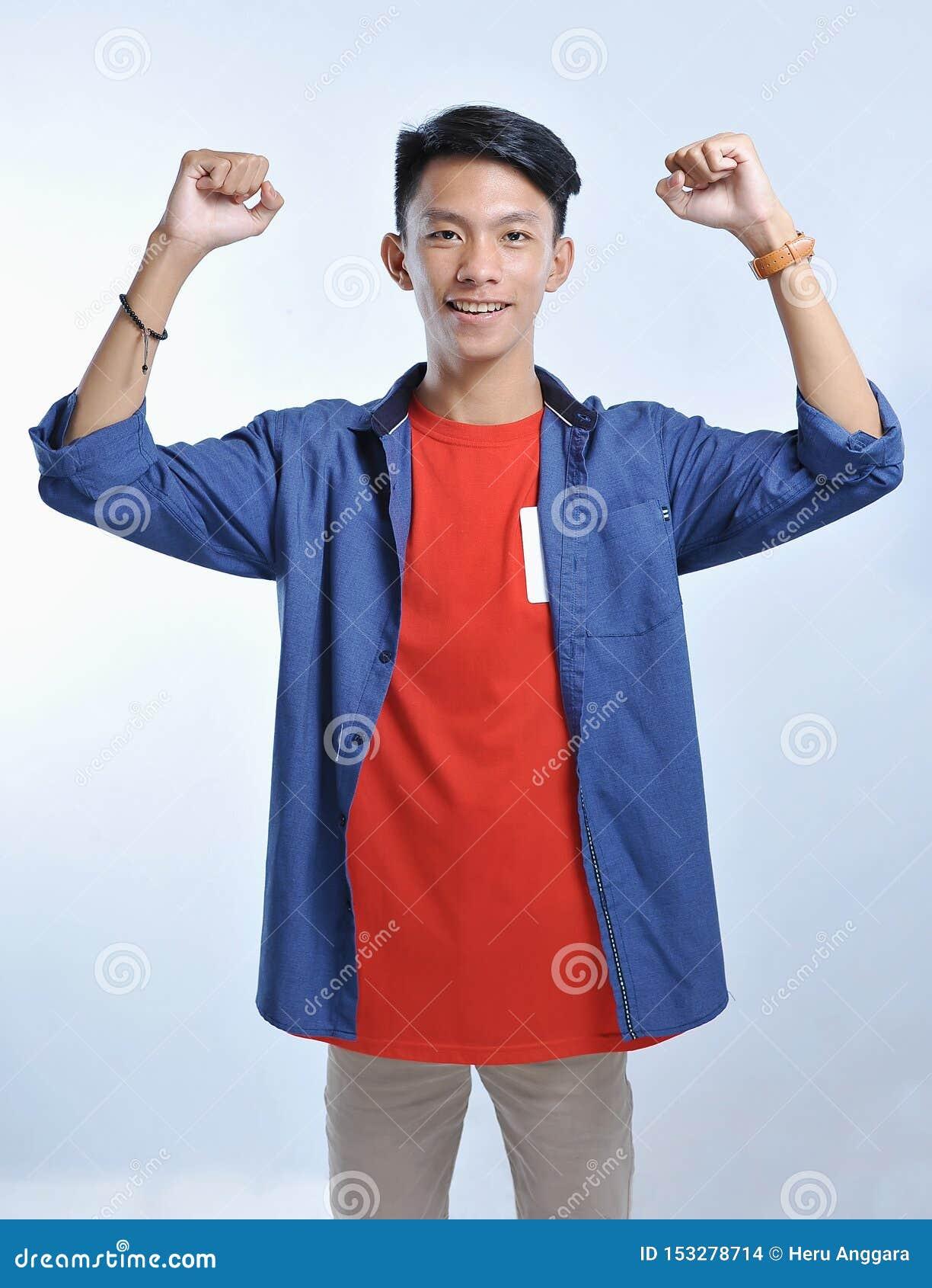 Человек доверия азиатский молодой нести случайные футболки с уверенный усмехаться