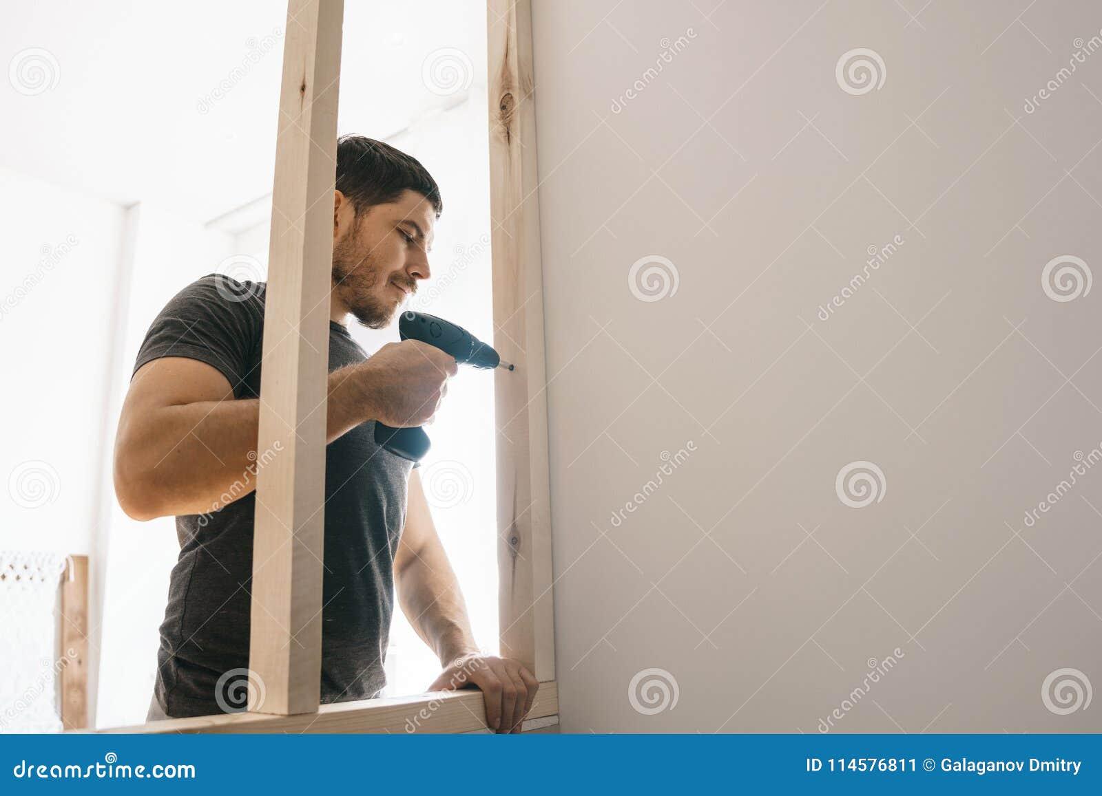 Человек доволен при отвертка, фиксируя деревянную рамку для окна к светлой стене Отремонтируйте