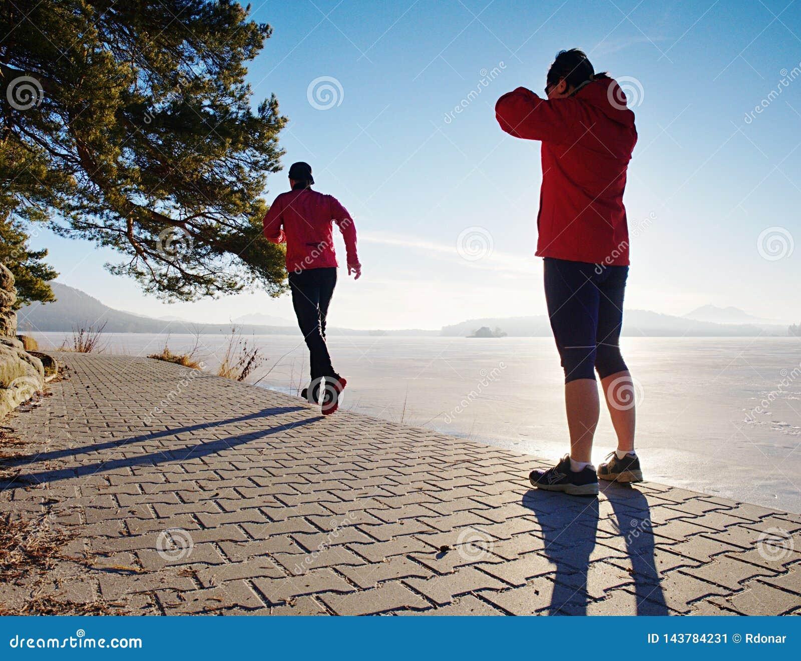 Человек женщины folowing идущий на пляже озера Команда бегунов