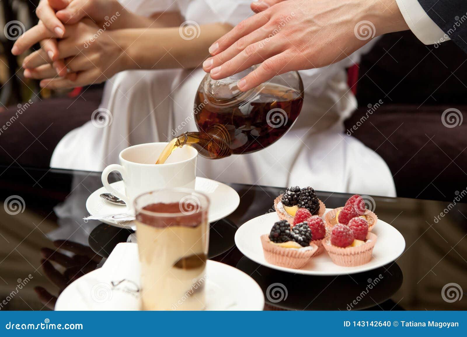 Человек заботит для женщины: льет ее зеленый чай На таблице десерты: тирамису и печенья со свежими ягодами Без сторон