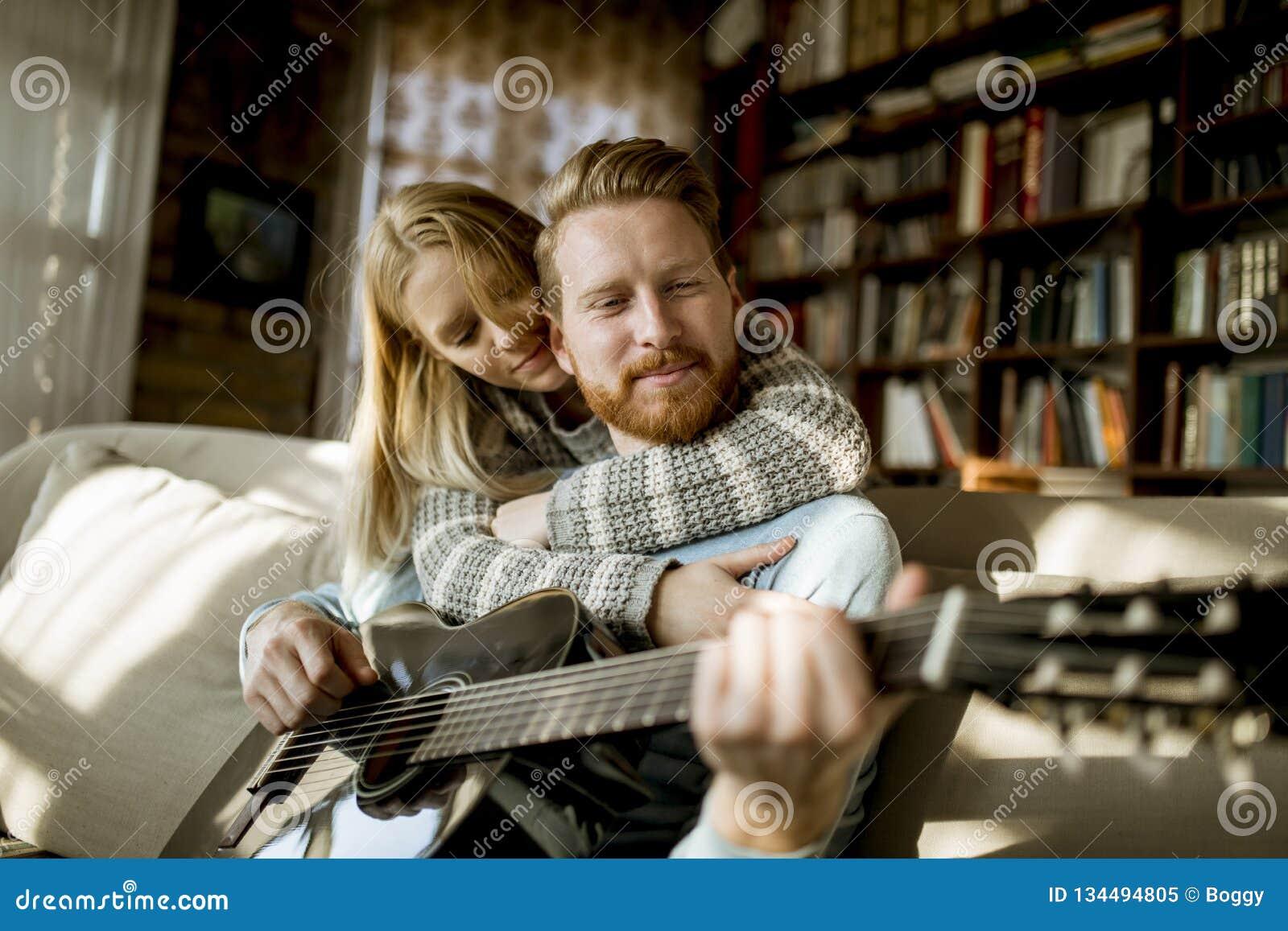 Человек играя акустическую гитару на софе для его молодой красивой женщины