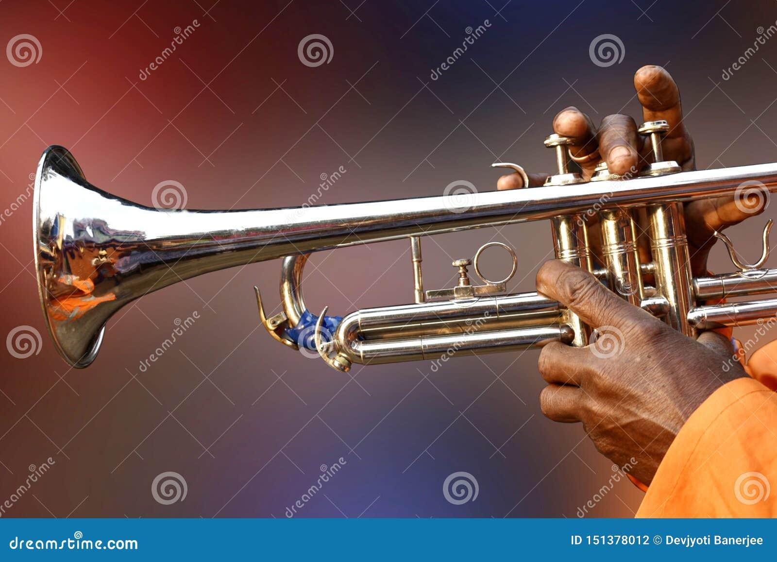 Человек играя сладкие песни с трубой, латунью, ветром, джазом, aerophone, аппаратурой музыки