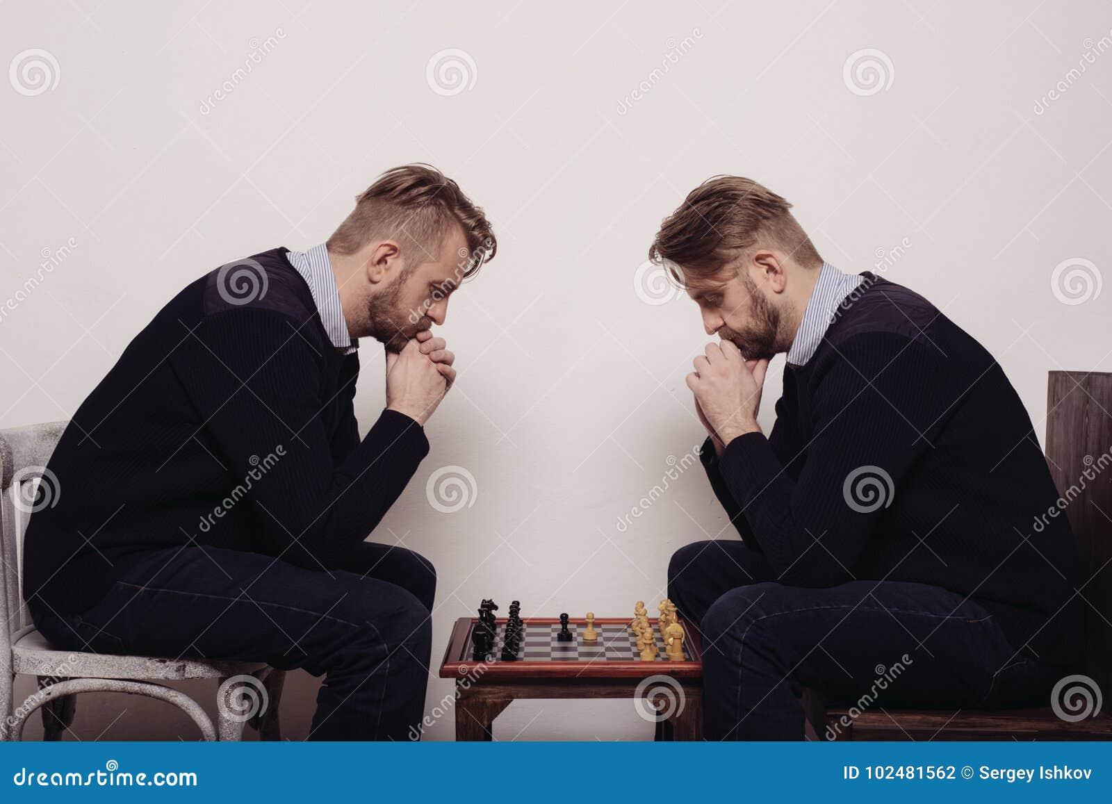 Человек играя шахмат против себя