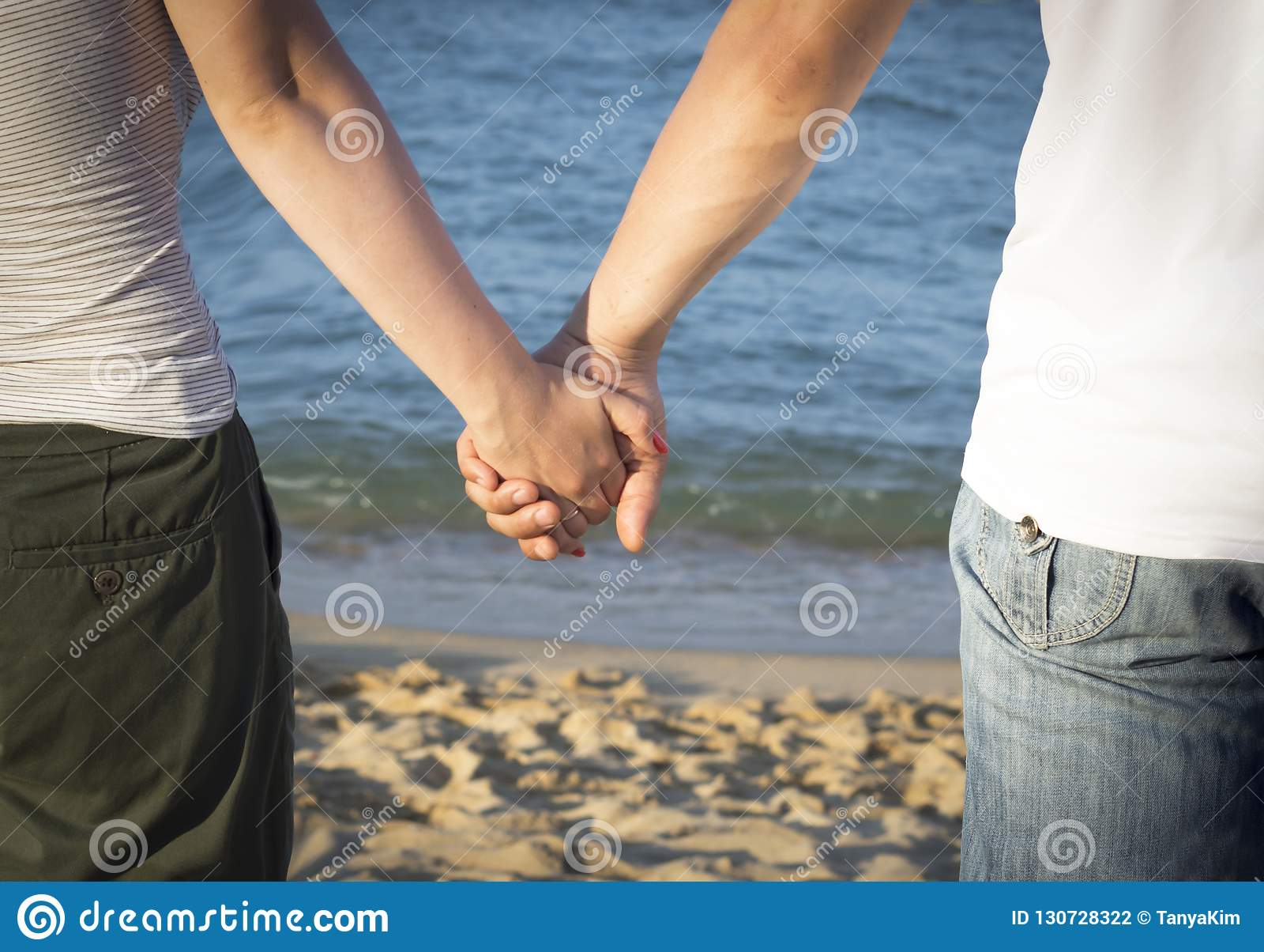 Человек и женщина держа руки против моря