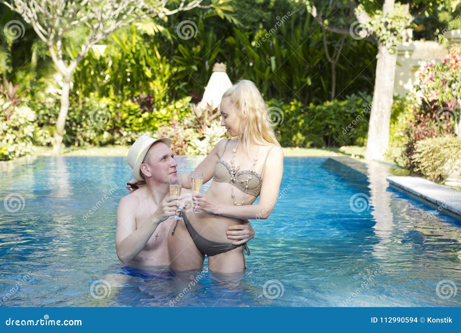 Человек и женщина, любящая пара, в бассейне в саде с тропическими деревьями держат стекла с вином в руке