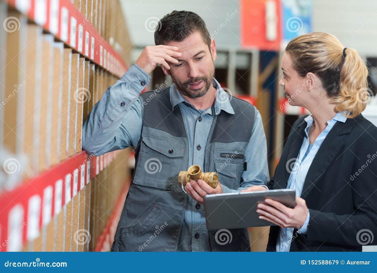 Человек и женщина портрета с планшетом в складе