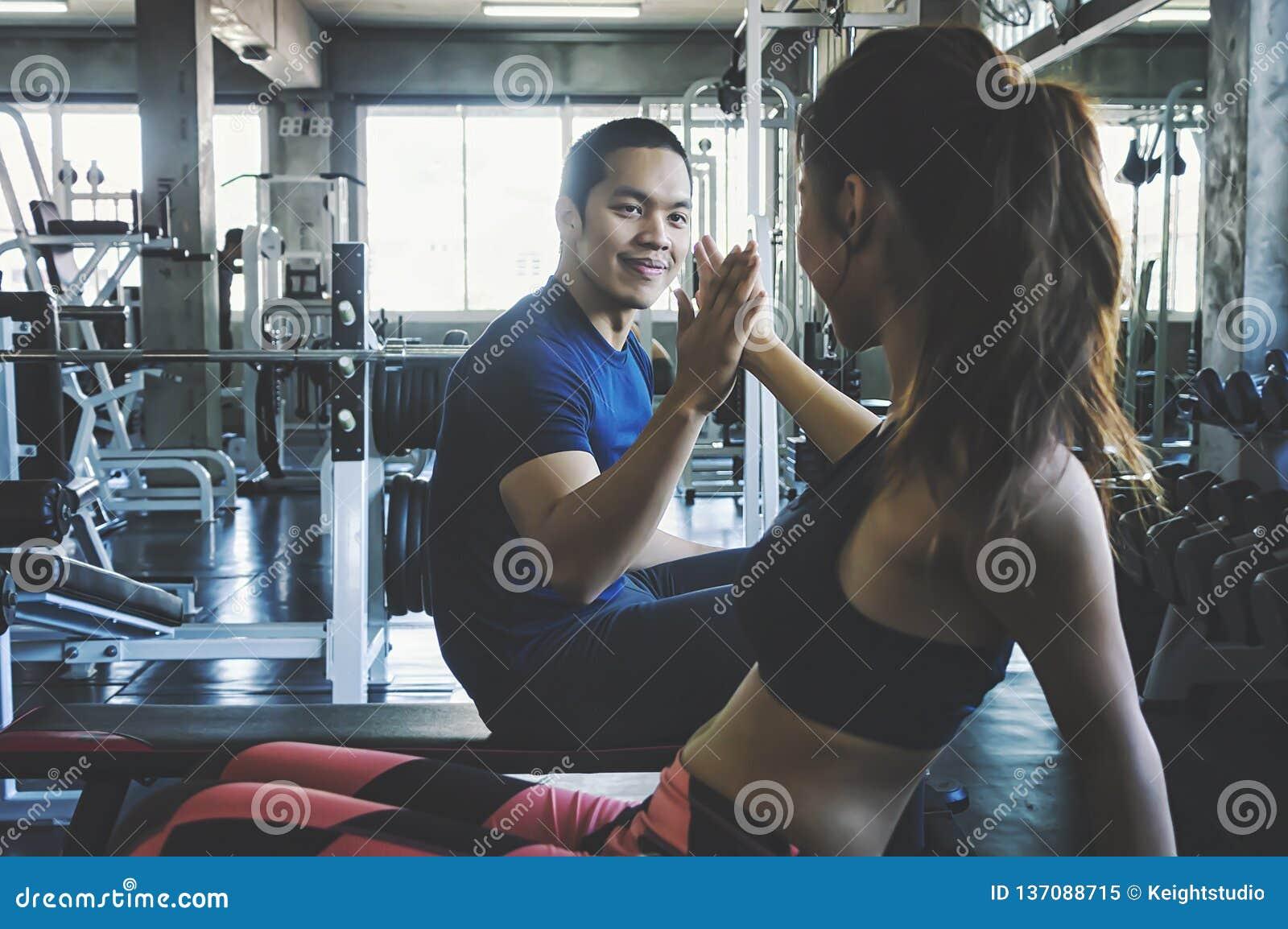 Человек и женщина фитнеса давая одину другого высокие 5 после встречи в спортзале Подходящие пары высокие 5 после разминки