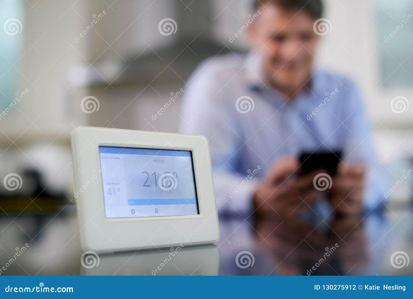 Человек контролируя метр центрального отопления умный используя приложение на черни