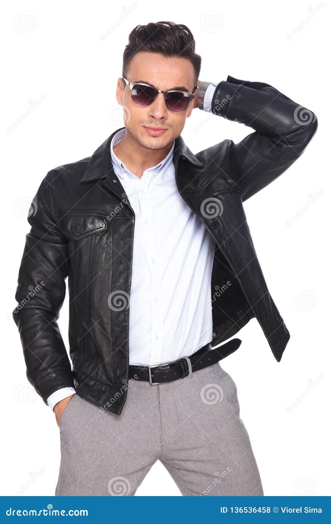 Человек моды нося солнечные очки аранжирует волосы пока стоящ