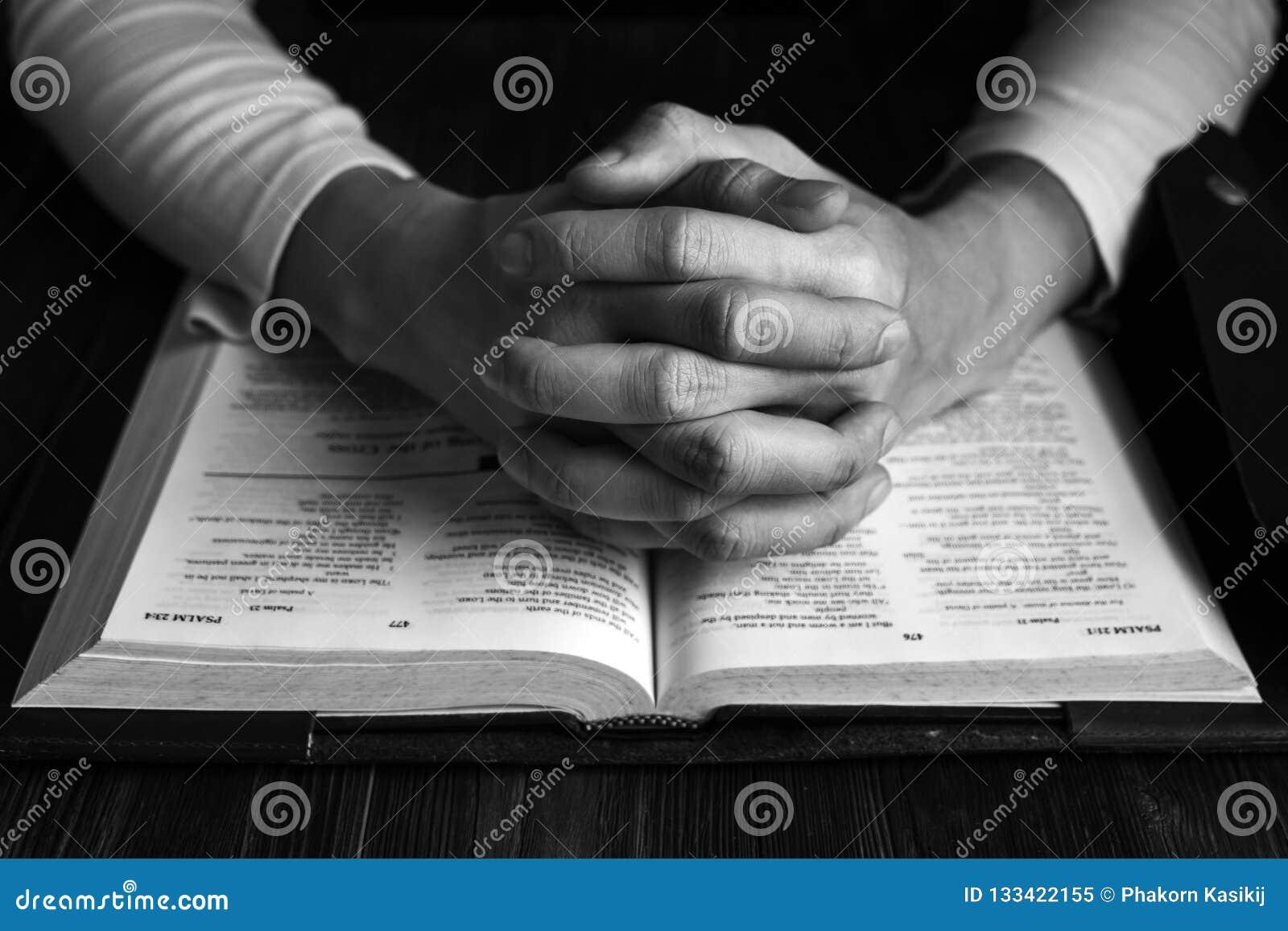 Человек моля к богу с его библией, молитве с чтением библии
