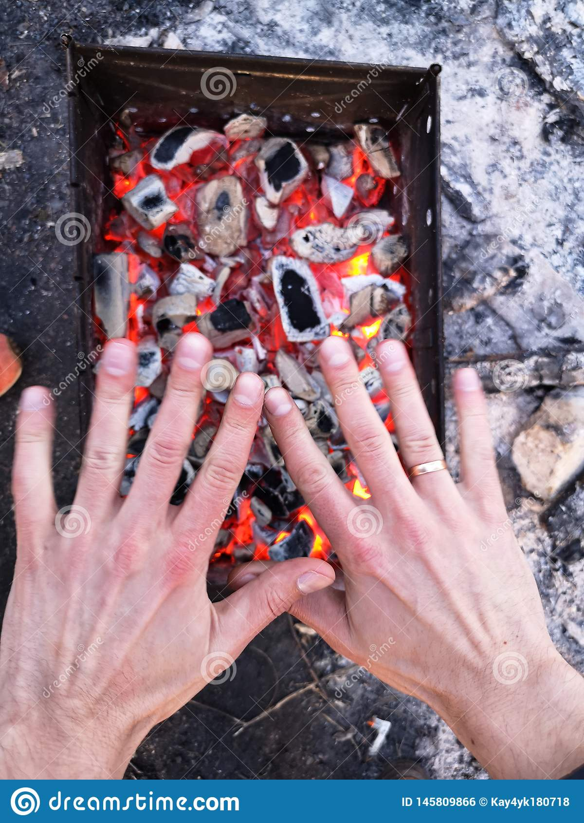 Человек нагревает его руки перед открытым огнем Располагаясь лагерем концепция с на открытом воздухе открытыми пламенами огня Тур