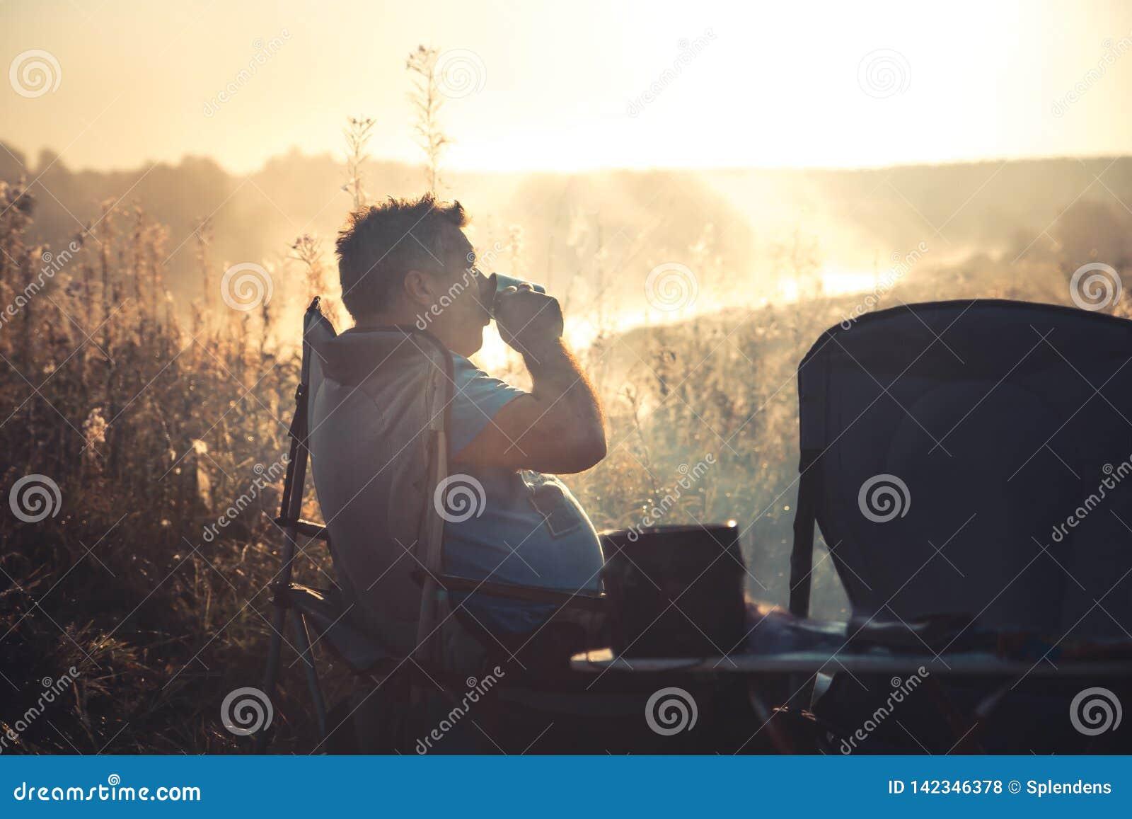 Человек наслаждается выпить кофе outdoors сидя в стуле во время туманного восхода солнца утра на образе жизни места для лагеря ра