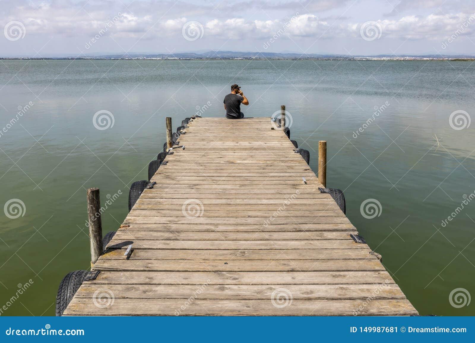 Человек на доке озером на небе утра