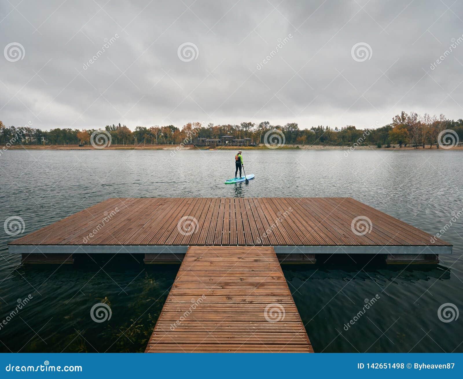 Человек на стойки paddleboard вверх