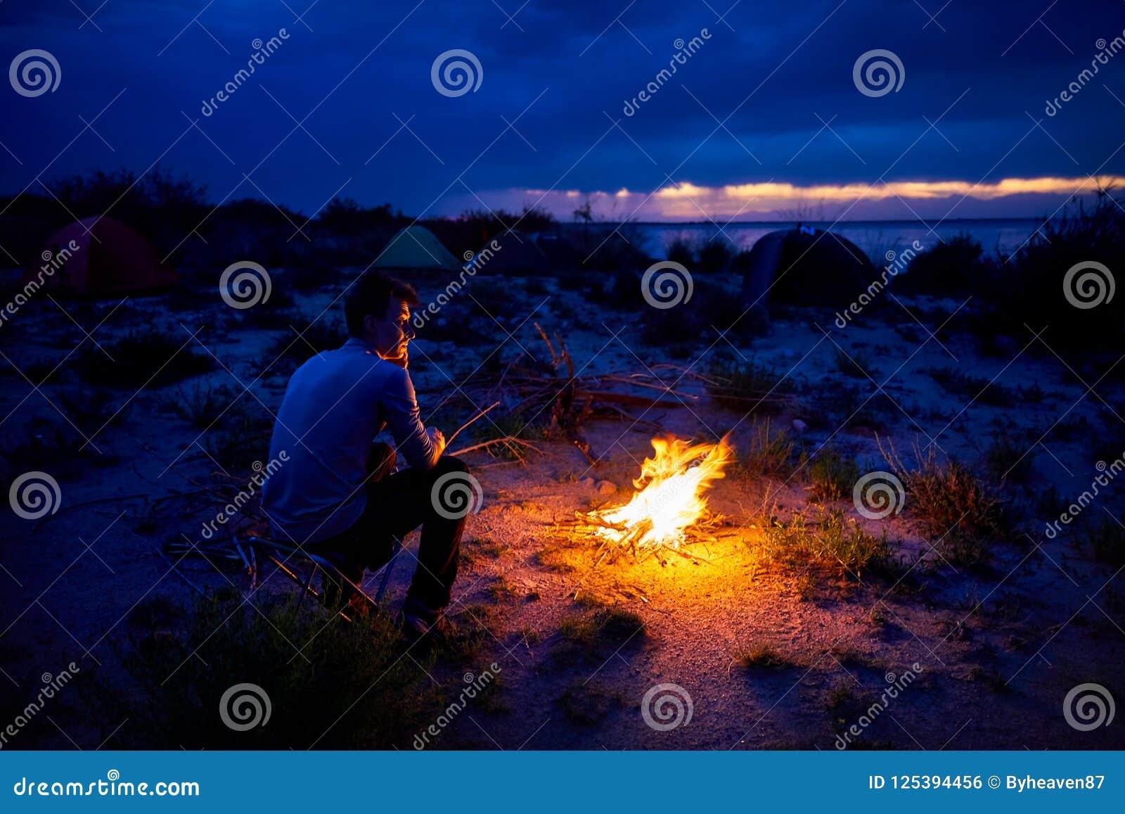 Download Человек около лагерного костера Стоковое Фото - изображение насчитывающей hiker, backhoe: 125394456