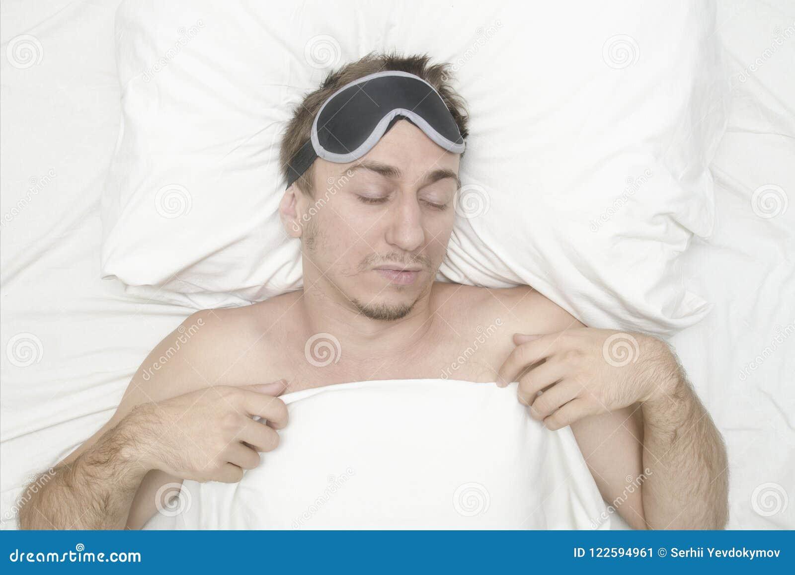 Человек отдыхая в маске для сна Стерня на его стороне утомлянный человек