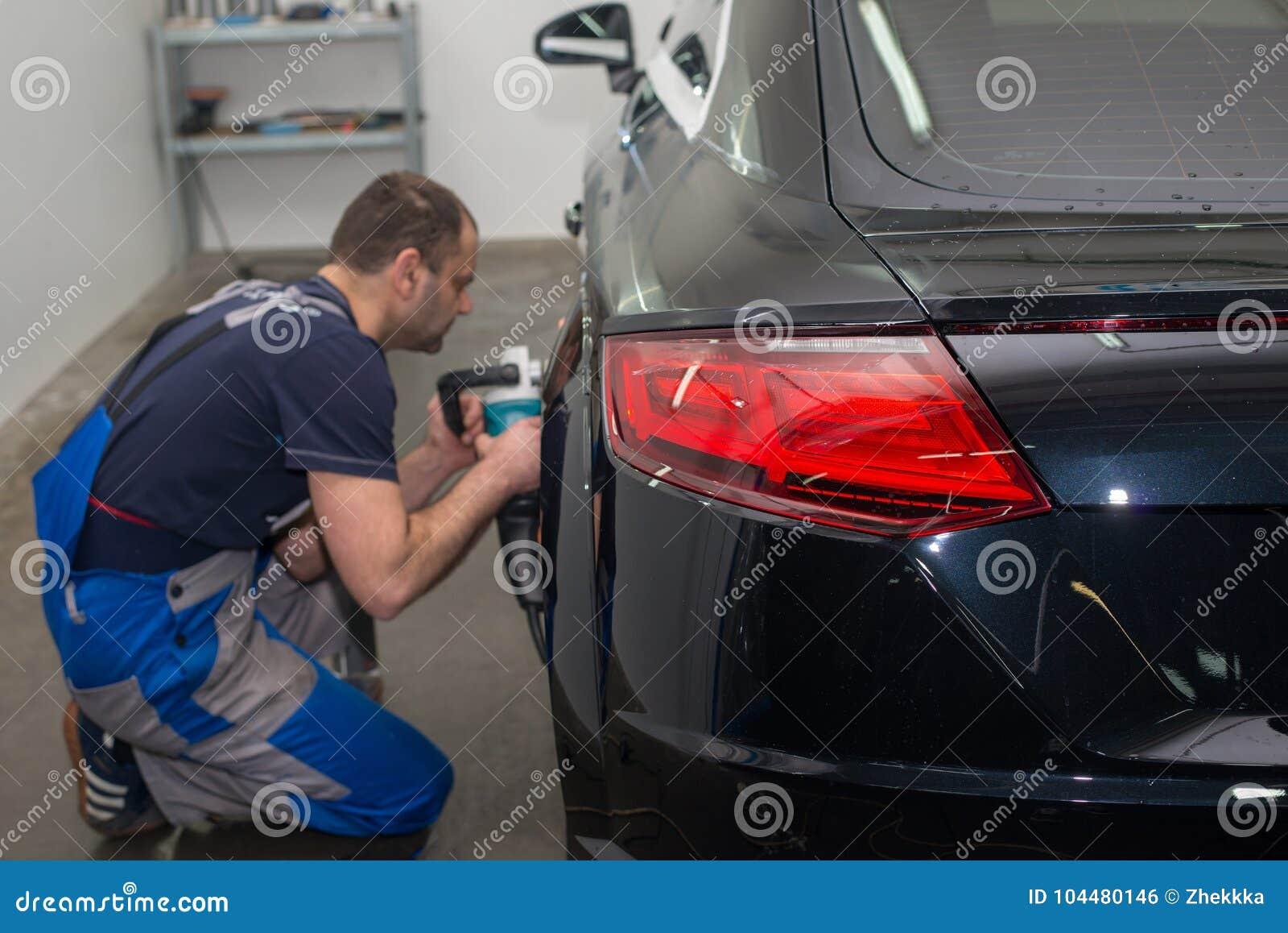 Человек полирует черный автомобиль
