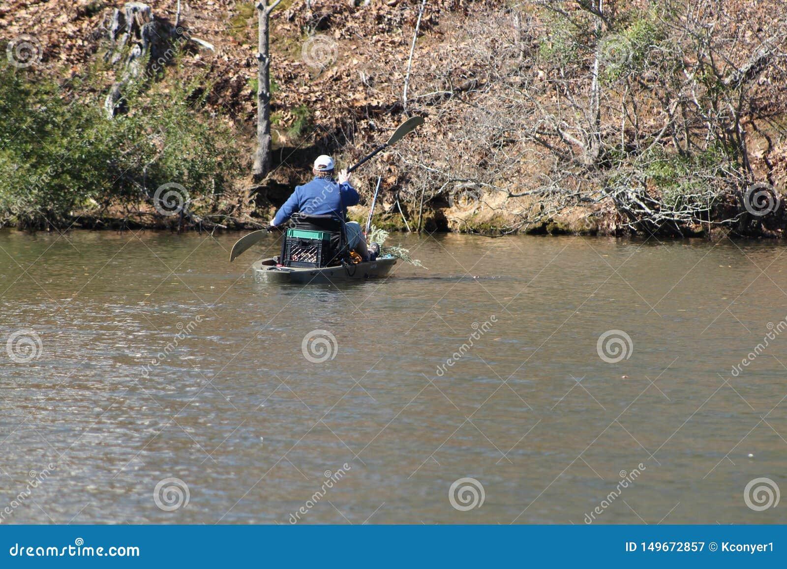 Человек полоща в его маленькой лодке