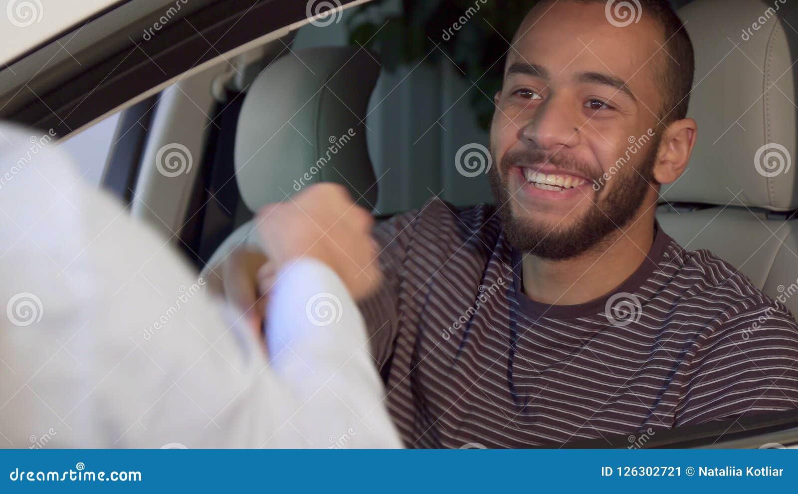 Человек получает ключ автомобиля на дилерских полномочиях