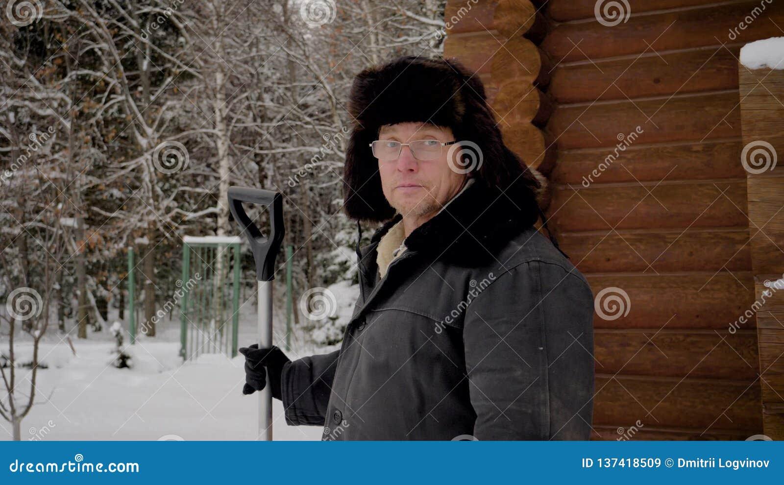 Человек портрета в шляпе и теплых одеждах стоя в зиме дома и держать лопаткоулавливатель акции видеоматериалы