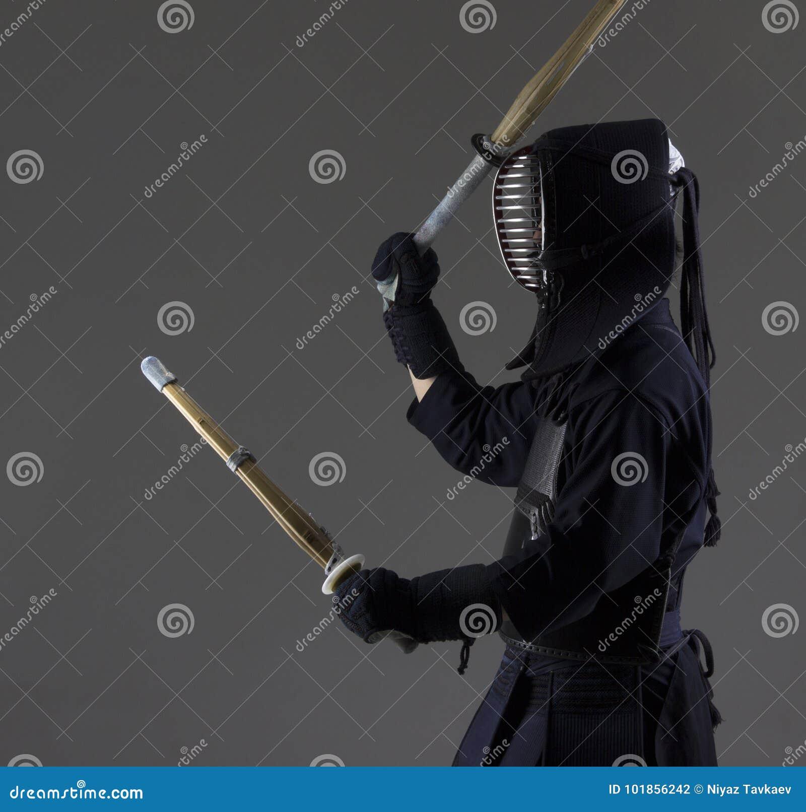 Человек практикует kendo в традиционном панцыре Он отбрасывая с 2 бамбуковыми шпагами