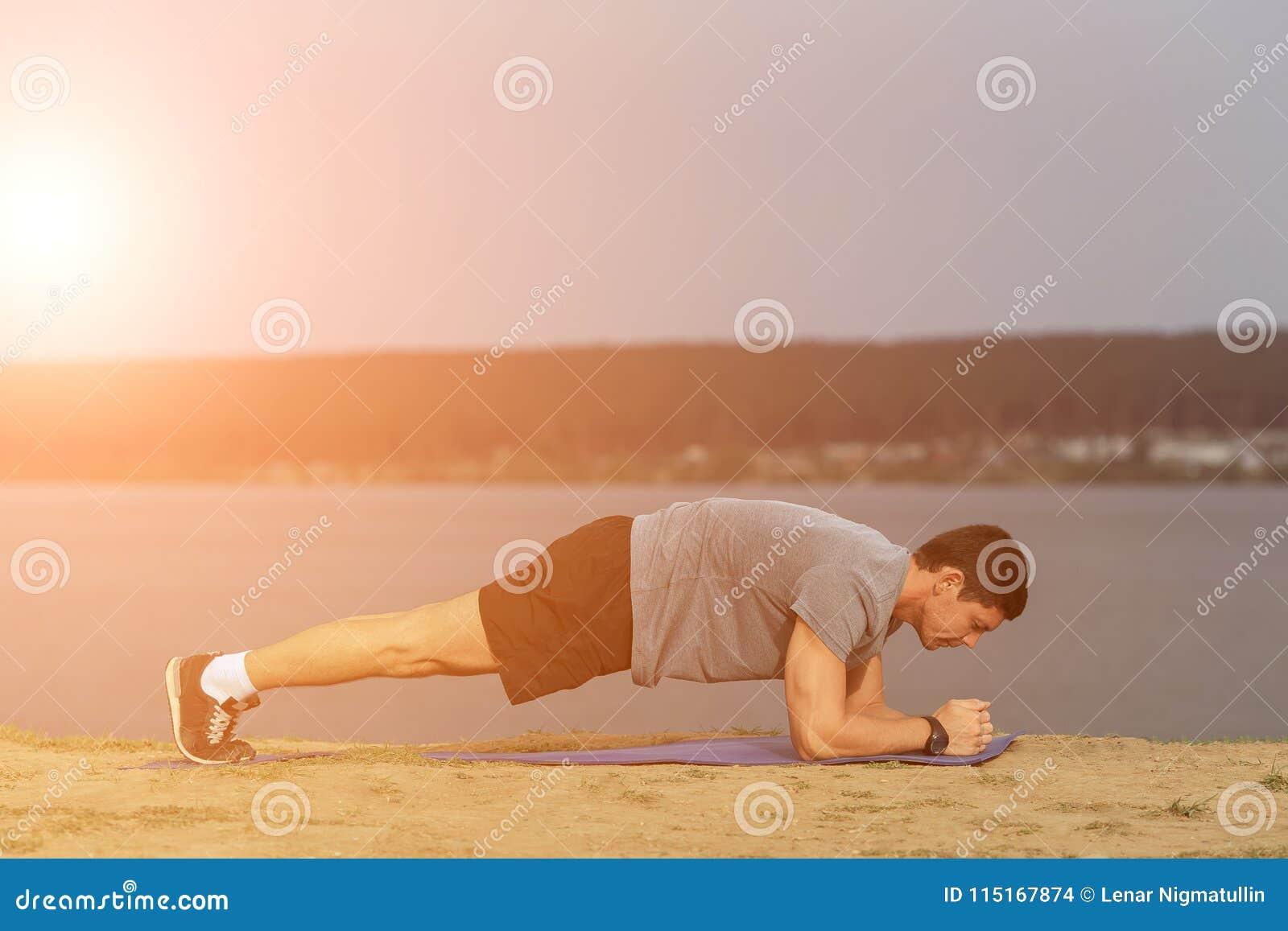 Человек пригодности тренировки Crossfit делая тренировку ядра планки разрабатывая его ядр midsection muscles Подходящая мужская п