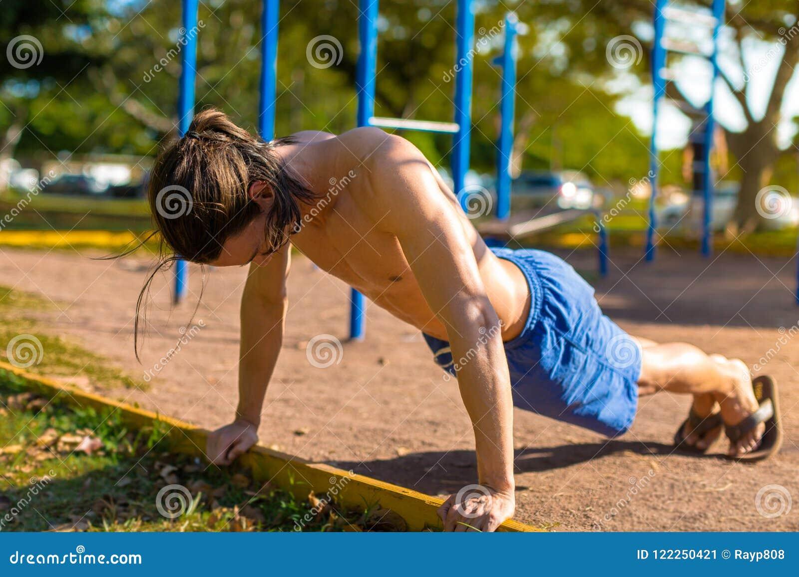 Человек пригонки работая на внешнем спортзале на парке Делать нажимает поднимает