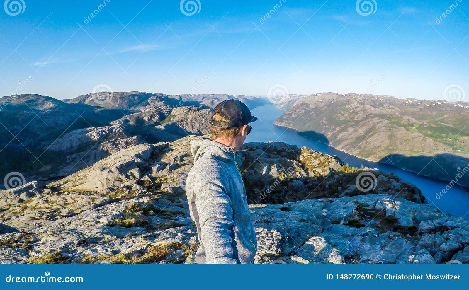 Человек принимая selfie и вдоль фьорда в Норвегии