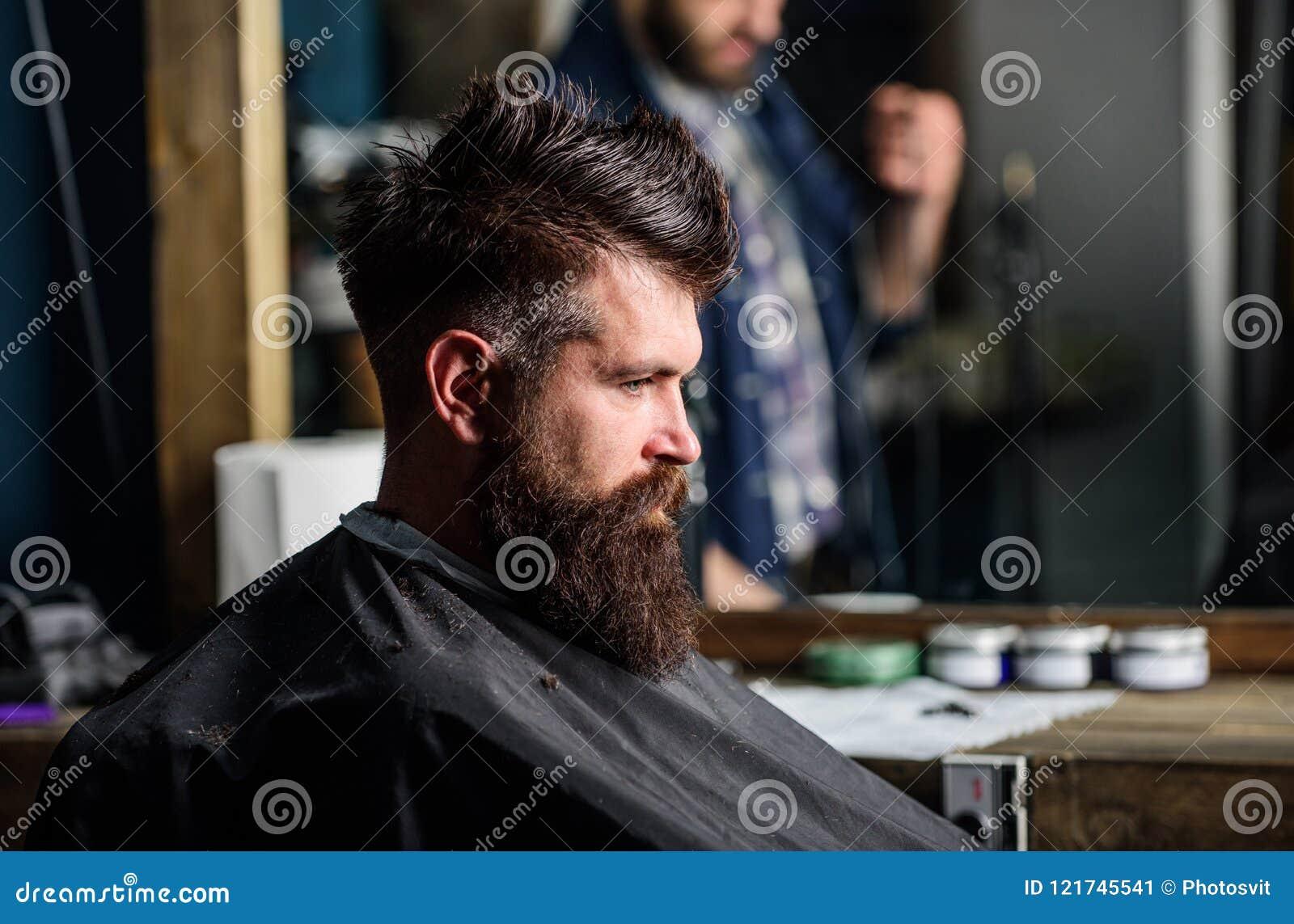 Человек при борода покрытая с черной накидкой сидит в стуле парикмахеров, предпосылке зеркала Битник с бородой ждет