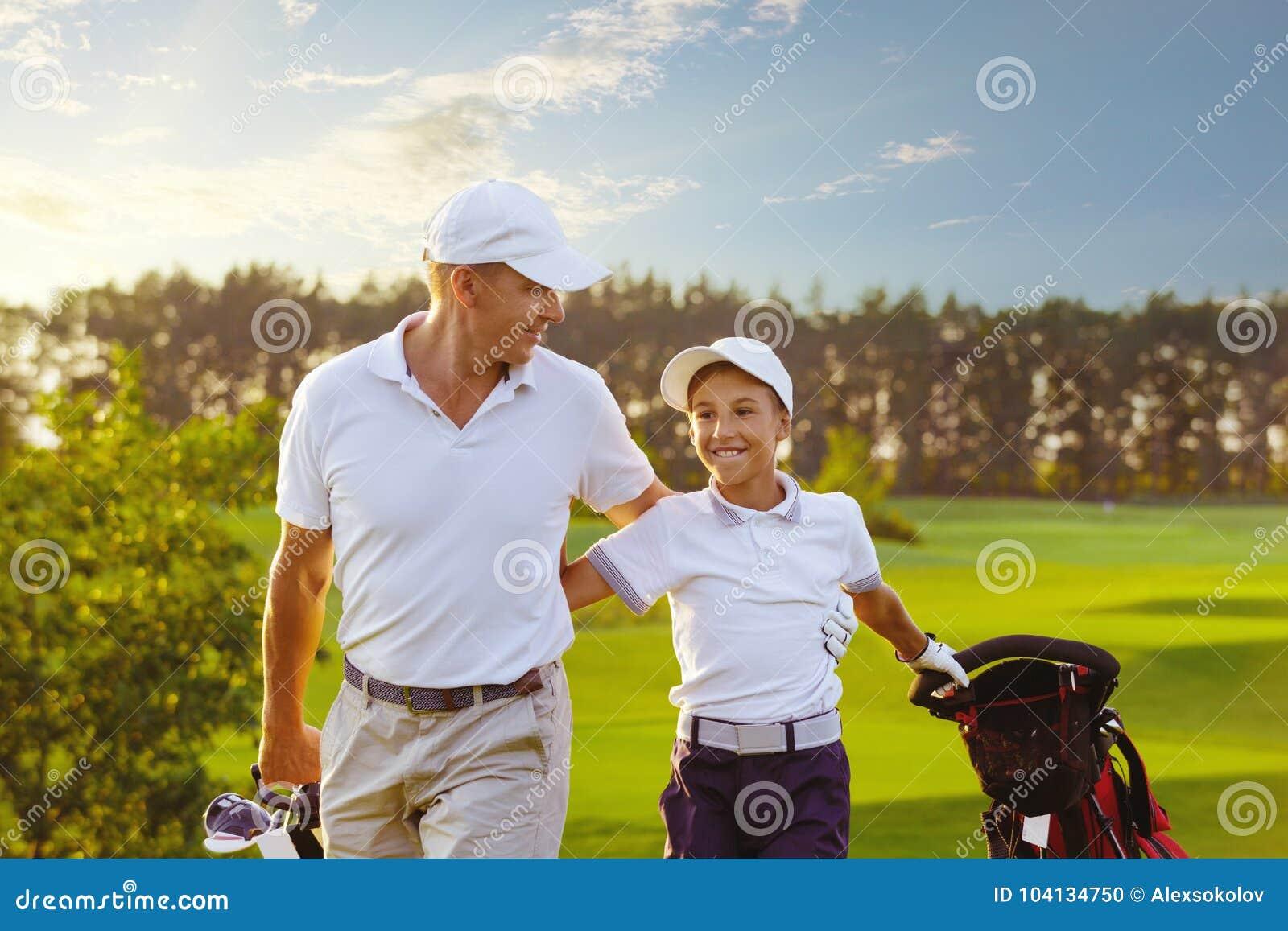 Человек при его игроки в гольф сына идя на поле для гольфа