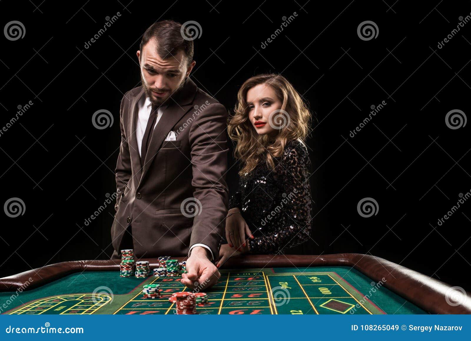 Человек при женщина играя рулетку на казино Наркомания к