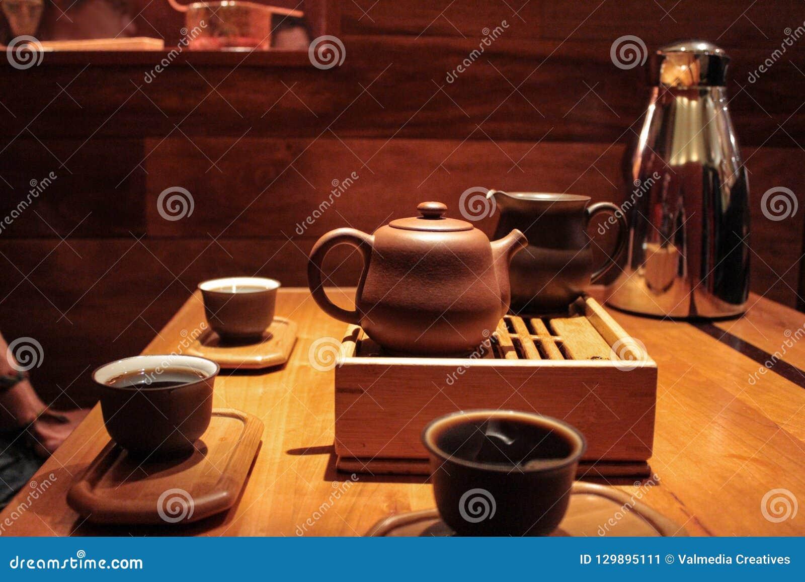 3 человек пробуя и выпивая очень темный чай pu-erh в небольшие пробуя чашки