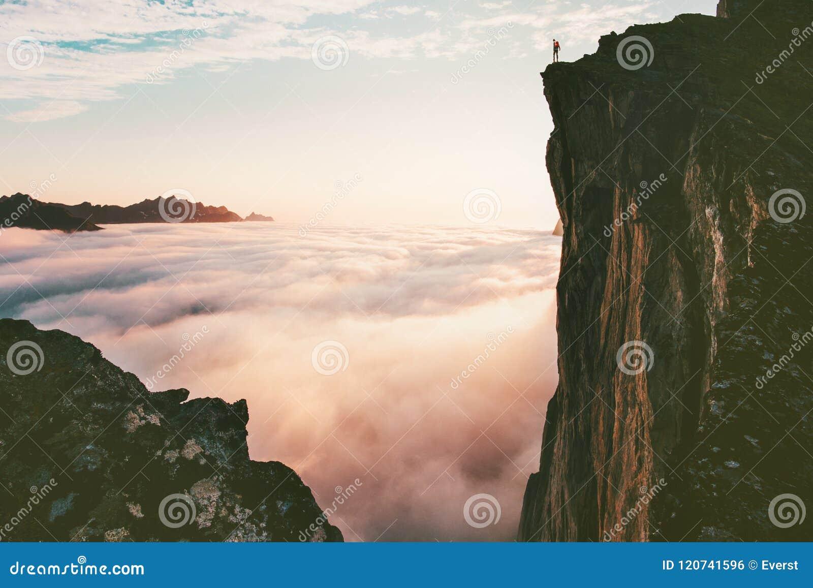 Человек путешественника стоя на скале края над облаками