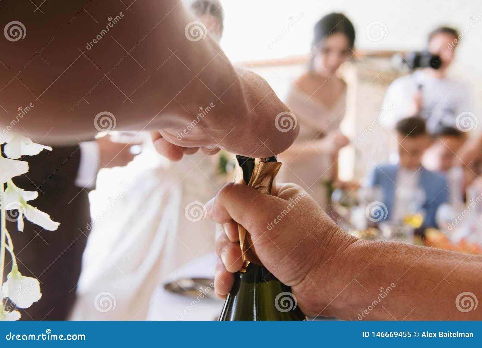 Человек раскрывает бутылку uo конца шампанского