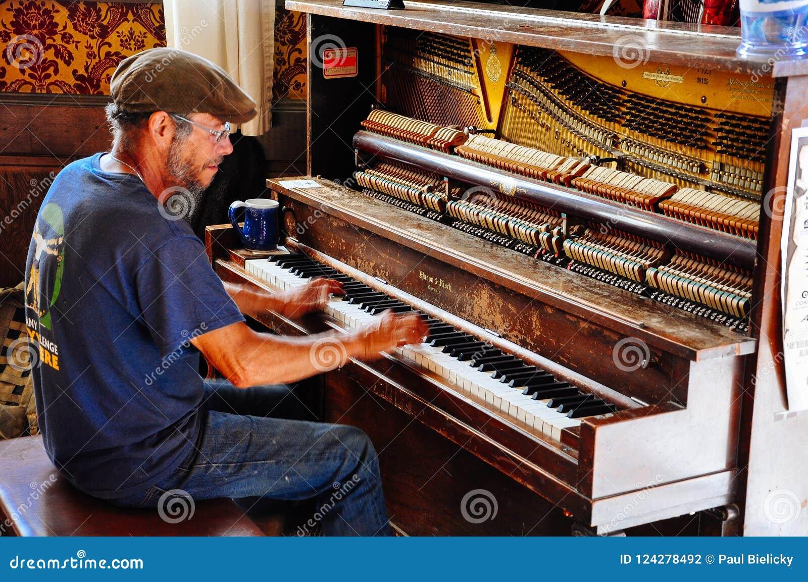Человек рояля внутри городской гостиницы в городе Dawson, Юконе