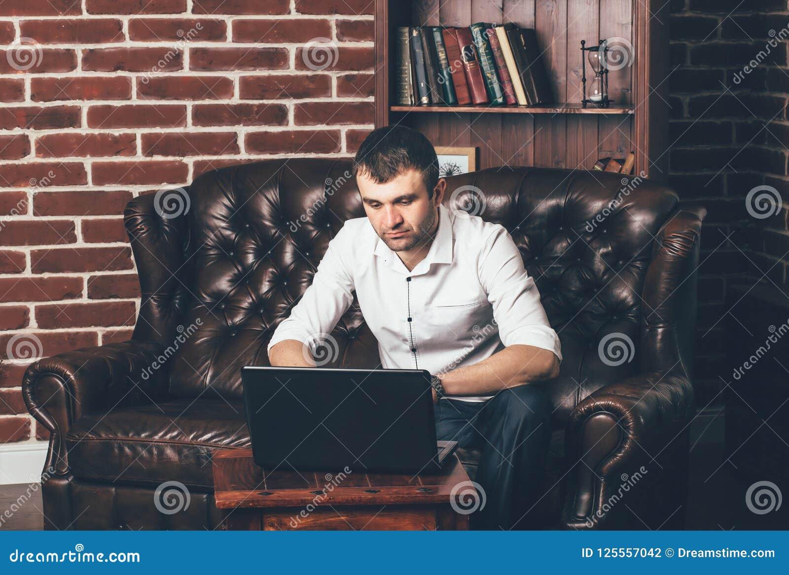 Человек сидит на роскошной софе и работает за ноутбуком в его офисе на предпосылке книжных полков