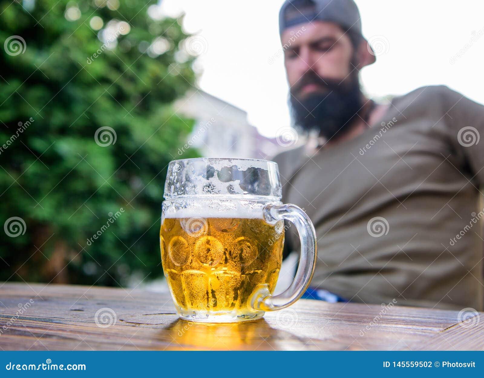 Человек сидит терраса кафа наслаждаясь пивом defocused Пиво ремесла молодо, городской и модно Отдельная культура пива Кружка