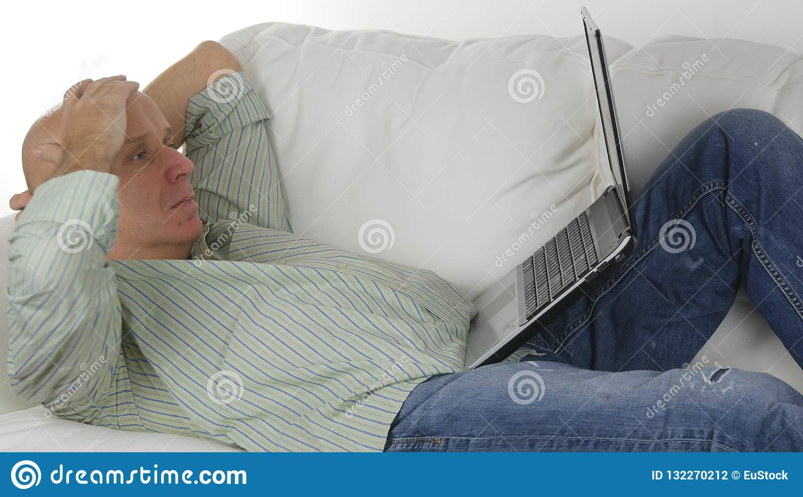Человек сидя на софе делая дело используя ноутбук делает разочарованные жесты