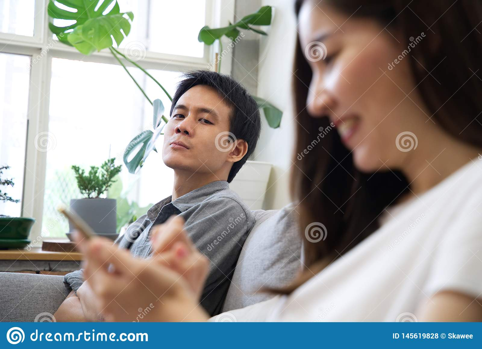 Человек сидя на софе чувствует несчастным с его девушкой
