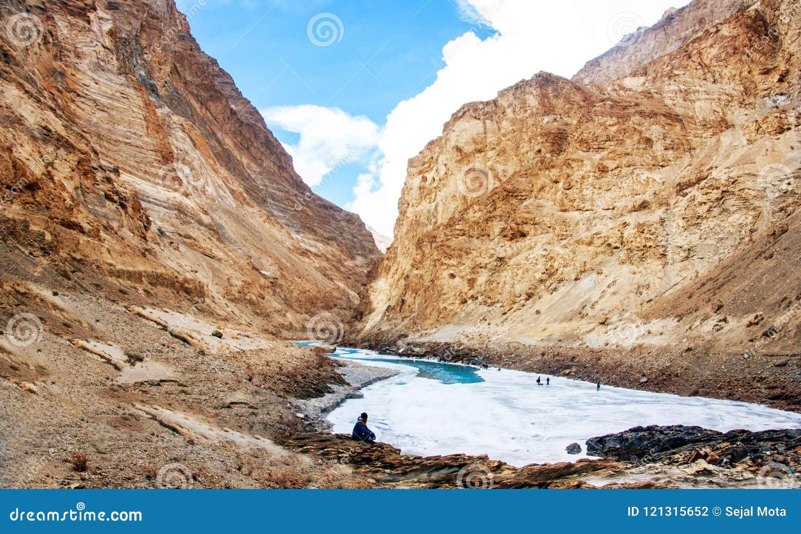 Человек сидя на стороне реки Замороженное река Zanskar и красивая гора Кривая текучести реки