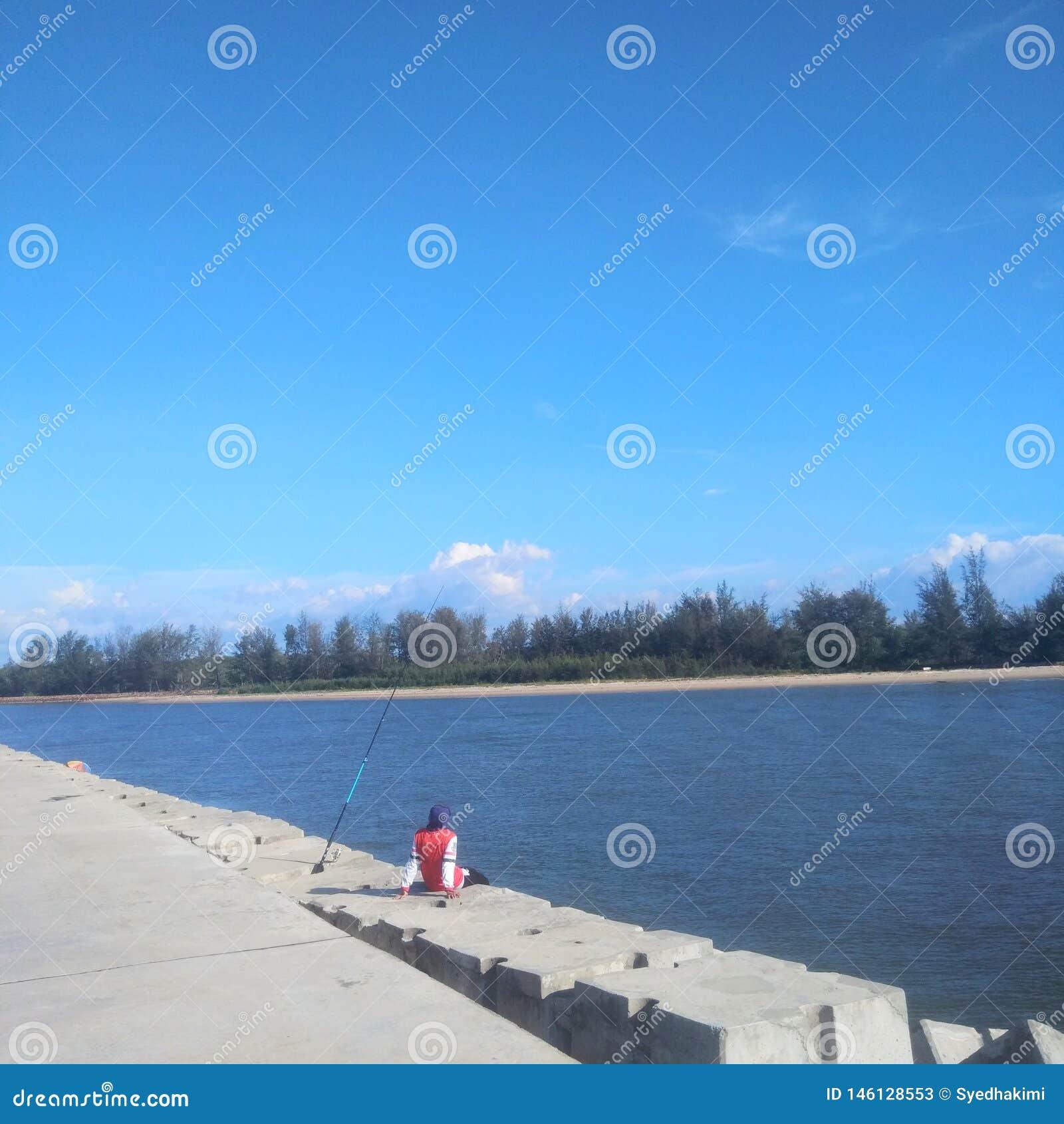 Человек сидя самостоятельно на рыбопромысловой деятельности на солнечный день - изображении пристани