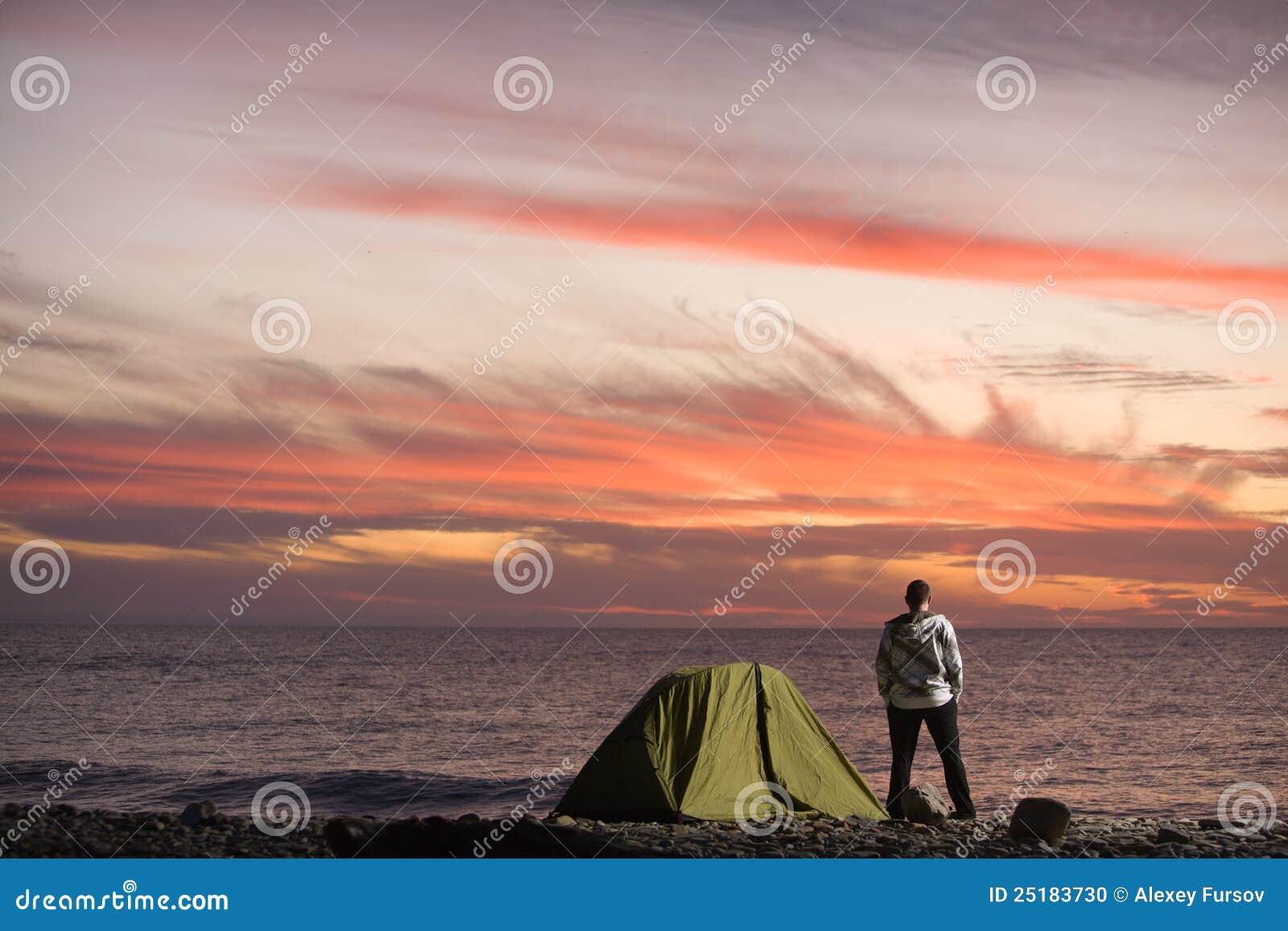 Человек смотря заход солнца