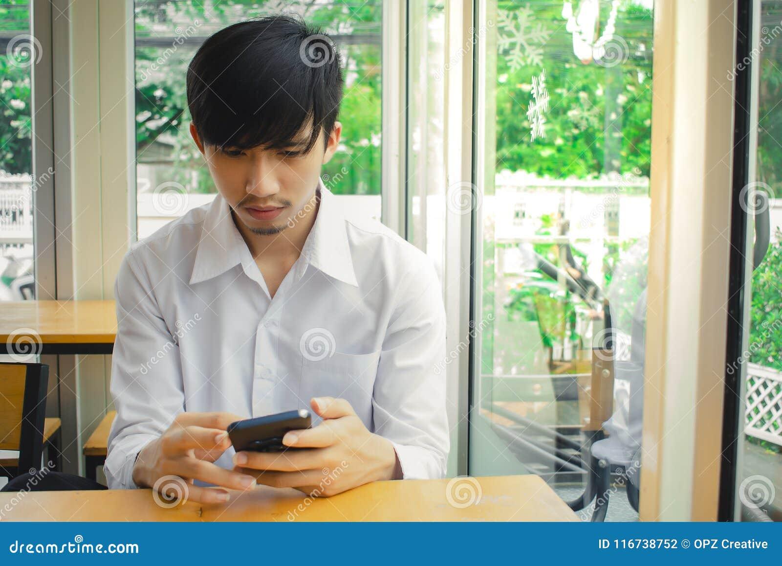 Человек смотря смартфон около окна