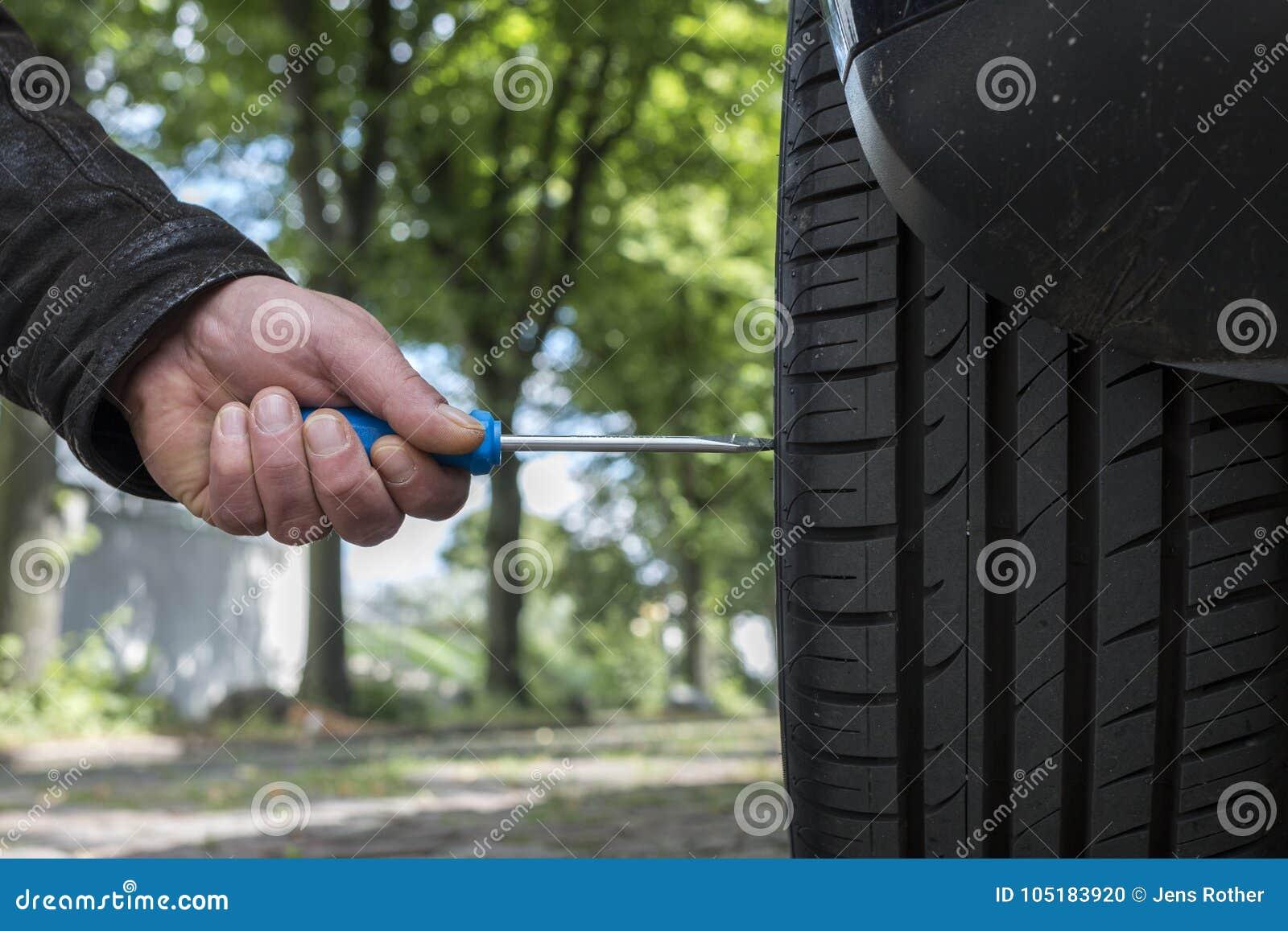 Человек сокрушает автошину автомобиля
